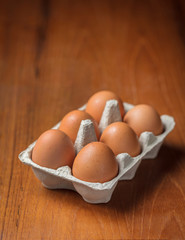 Brown eggs in cardboard on table