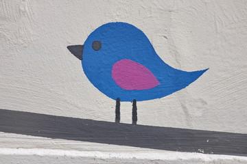 Oiseau coloré sur une branche peint sur un mur