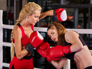 Two boxing women workout in fitness class. Sport exercise two female people. Boxer wearing red gloves to box in ring. Girlfriends train together.