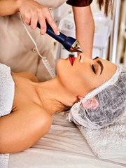 Ultrasonic facial treatment on ultrasound face machine. Woman has electric lift massage spa salon. Stimulation muscles by professional equipment microcurrent therapy. Removing wrinkles.