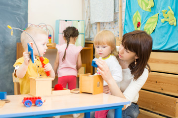 kids group playing with teacher in day care centre playroom