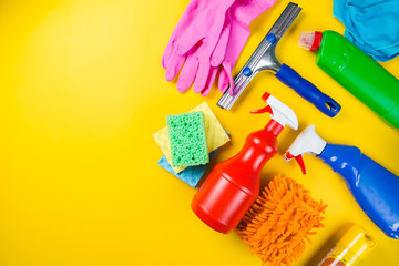 Cleaning concept - cleaning supplies on wood background