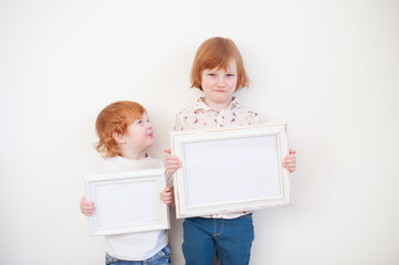 Two redhead children with frames in their hands