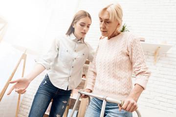 Girl is nursing elderly woman at home. Woman is standing with help of walker.