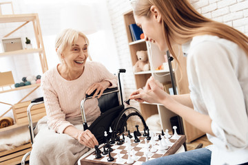 Girl is nursing elderly woman at home. They are playing chess.
