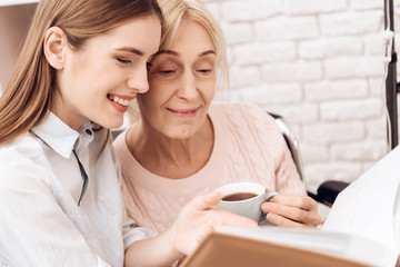 Girl is nursing elderly woman at home. They are looking at photos in photo album.