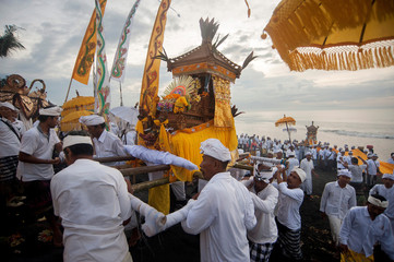 Balinese Hindu carry sacred statues of gods and deities during a Melasti purification ceremony ahead of Nyepi, on Purnama Beach, Gianyar, Bali