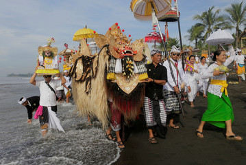 Balinese Hindu carry sacred statues of gods and deities during a Melasti purification ceremony ahead of Nyepi on a beach in Gianyar, Bali