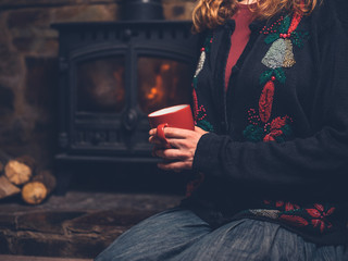 Woman in christmas jumper with mug by fire