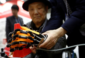 Yook Ki-dong from South Korea tries on 'Power Assist Hand', rehabilitation robot for paralyzed hands, at Tokyo CareWeek 2018 in Tokyo