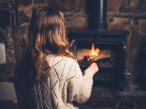 Young woman poking a fire