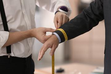 Tailor taking man's measurements in atelier