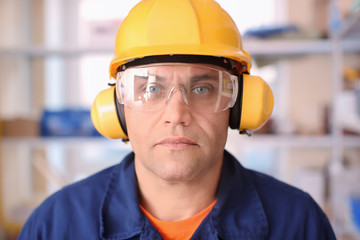 Male worker with hearing protectors and safety goggles, indoors