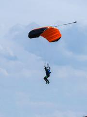 Parachutist with Orange Parachute against Clear Blue Sky