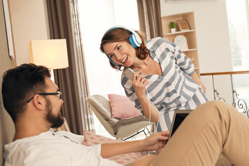 Lovely couple together at home. Woman dancing with headphones while her man lying on bed