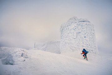 Man hiking with backpack and snowshoes in winter mountain