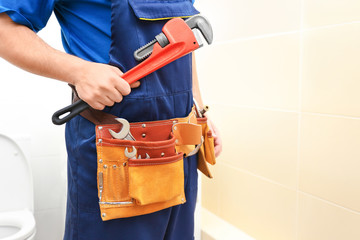 Plumber with set of tools in restroom