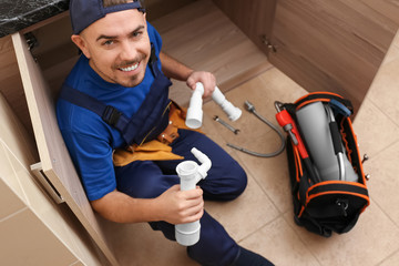Plumber with set of tools working in kitchen
