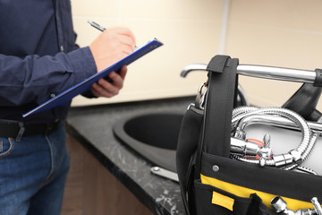 Plumber with set of tools and clipboard in kitchen
