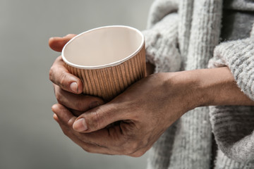 Poor woman with cup on grey background