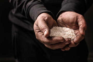 Poor man holding rice in hands on dark background