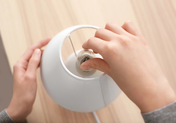 Woman changing light bulb in lamp at home