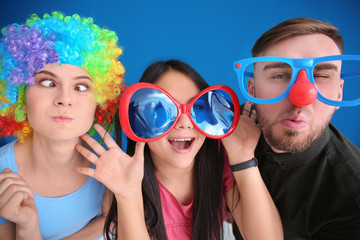 Young people in funny disguise posing on color background. April fool's day celebration