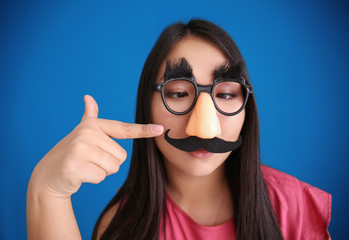 Young woman in funny disguise posing on color background. April fool's day celebration