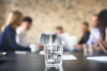 Glass of water and blurred office meeting on background. Finance trading