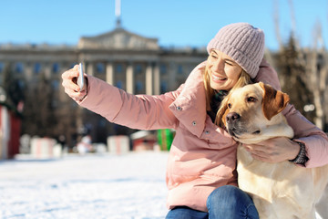 Woman taking selfie with cute dog outdoors on winter day