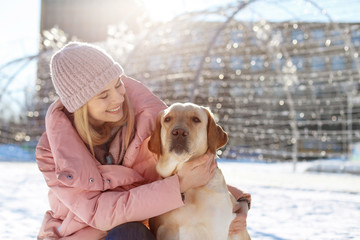 Portrait of woman hugging her cute dog outdoors on winter day. Friendship between pet and owner