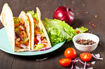 Mexican food, corn tortillas with fried chicken fillet, fresh salsa and vegetables on a dark background, close-up. A healthy diet, without gluten, a menu for a cafe.