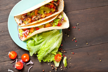 Mexican food, corn tortillas with fried chicken fillet, fresh salsa and vegetables on a dark background, top view. Healthy diet, gluten free, weight loss concept