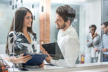 Smiling businesswoman and handsome businessman having informal meeting in office