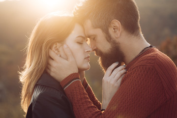 Man with beard holds womans head with tenderness, close up.