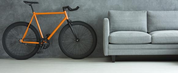Orange bicycle in grey living room interior