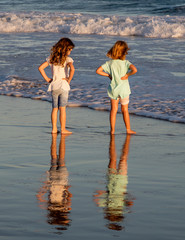 Two little girls playing in the shallow water of the sea late in the afternoon. Their reflections are clearly visible on the wet sand. The wind is blowing through their long hair