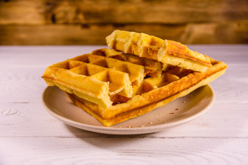 Ceramic plate with belgian waffles on wooden table