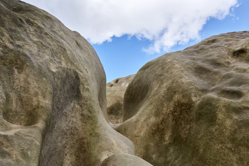 sandstone rock formation against sky with clouds