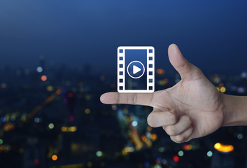 Play button with movie icon on finger over blur colorful night light city tower, Cinema online concept
