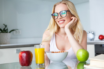 beautiful smiling young woman in eyeglasses eating breakfast at home
