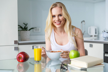 beautiful young woman eating muesli for breakfast and smiling at camera at home