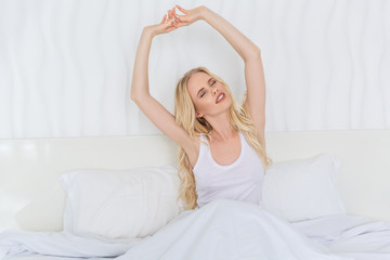 beautiful blonde girl stretching hands while sitting on bed at morning