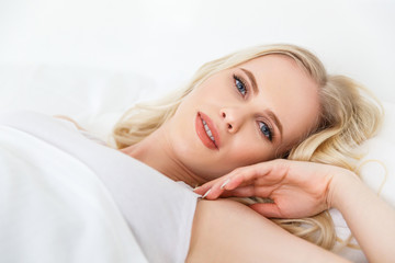 beautiful blonde girl lying in bed and looking at camera