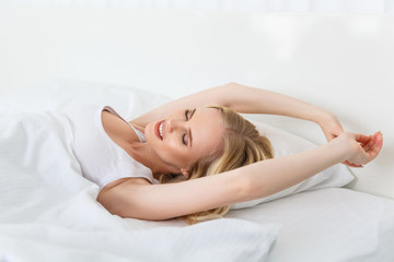 beautiful smiling blonde girl stretching in bed