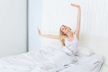 beautiful happy young woman waking up while sitting on bed