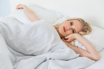 beautiful young blonde woman lying in bed and looking at camera
