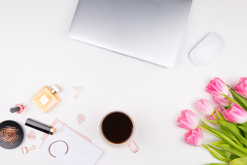 Decorative cosmetics, makeup tools, laptop, tulips and accessories on white background. Office and fashion concept. Flat lay composition, top view.