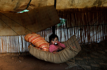 Palestinian girl sits in a makeshift bed inside her family's shelter in Jordan Valley in the occupied West Bank