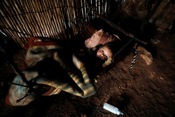 Palestinian boy lies in a makeshift bed inside his family's shelter in Jordan Valley in the occupied West Bank